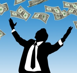 Shadowy figure in suit being showered with money